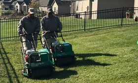 Two TenderCare employees mowing a lawn