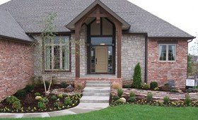 Beautiful front-facing view of a brick house, with a beautiful lawn in front