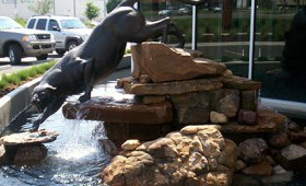 A statue of a jaguar stepping off some rocks with water pouring out of its mouth