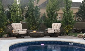 Poolside with beige chairs and a brown patio table with green trees behind the pool's fence