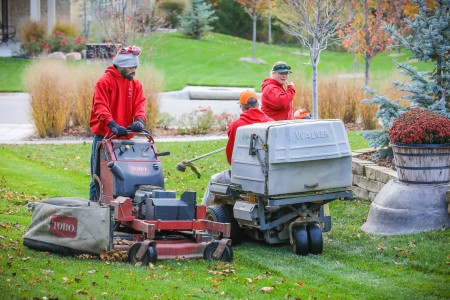 Two TenderCare employees mowing and bagging grass leaves