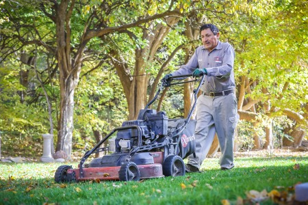 TenderCare employee mowing a beautiful lawn of grass