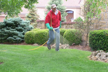 Man spraying grass with nutrients
