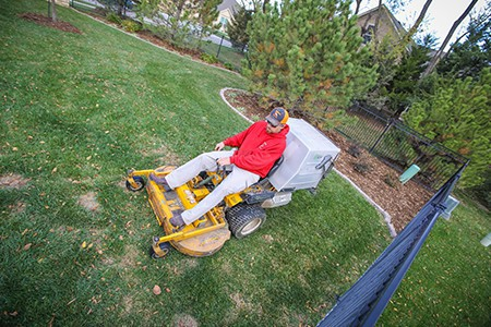 TenderCare employee mowing a lawn right beside a fence. The angle is a dutch tilt.