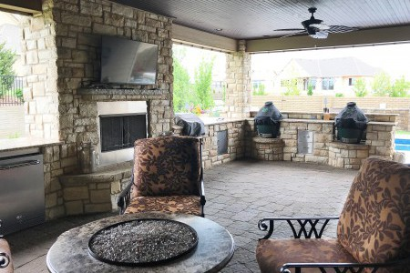 Enclosed stone patio with fireplace and fire pit