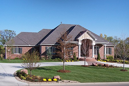 A scenic picture of a beautiful brick home with a beautiful lawn in front