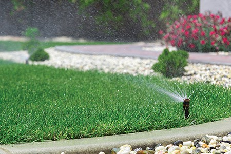 A sprinkler spraying on a small patch of beautiful green grass