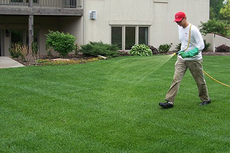 TenderCare employee watering a lawn