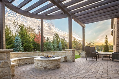Side angle of a beautiful patio with a firepit, table and chairs